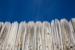 Vieille frontière de sécurité en bois et ciel bleu lumineux Photos libres de droits