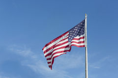 Vieille gloire de grand indicateur des États-Unis soufflant dans un vent violent un jour sans nuages S Indicateur Photographie stock libre de droits