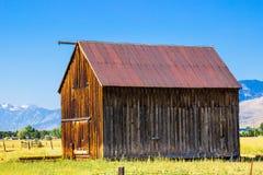 Vieille grange en bois en vallée au-dessous des montagnes Photographie stock libre de droits