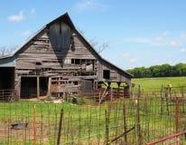 Vieille grange en bois par une barrière rouillée Images stock