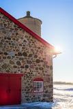 Vieille grange en pierre avec la porte rouge lumineuse et le Sunflare Photographie stock libre de droits