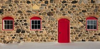 Vieille grange en pierre avec la porte rouge lumineuse et trois Windows Image libre de droits