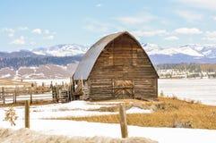 Vieille grange sur une route de campagne neigeuse Photos libres de droits