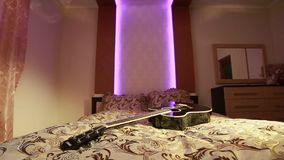 Vieille guitare coupée acoustique poussiéreuse dans le lit dans une chambre à coucher de ternissure banque de vidéos