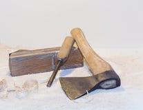 Vieille hache, avion, burin et copeaux en bois sur un fond clair Images libres de droits