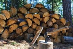 Vieille hache se tenant contre des morceaux empilés de bois de chauffage Photos stock
