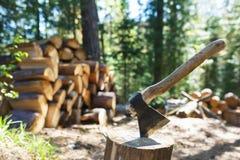 Vieille hache se tenant contre des morceaux empilés de bois de chauffage Photo stock