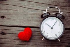 Vieille horloge avec le coeur rouge les temps en bois d'amour de table Images stock
