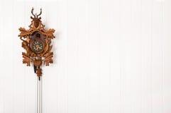 Vieille horloge de coucou en bois accrochant sur un mur blanc Photographie stock libre de droits