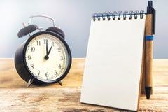 Vieille horloge noire et papier blanc avec le stylo, sur la table en bois Photographie stock libre de droits