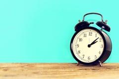 Vieille horloge noire, sur la table en bois Photo stock