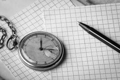 Vieille horloge, pages de papier dans une cage, un stylo sur un livre sage Concept d'éducation photo libre de droits
