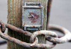Vieille horloge rouillée sur une chaîne image stock