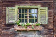 Vieille hutte alpine - fenêtre avec des fleurs Photographie stock libre de droits