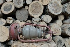 Vieille lampe à pétrole sur le fond du bois de chauffage photo stock