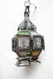 Vieille lampe cassée accrochée sur le mur blanc Image stock