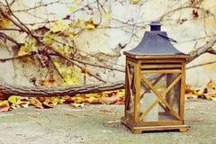 Vieille lampe en bois avec une bougie dans le jardin d'automne Image libre de droits