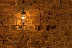 Vieille lampe légère la nuit accrochant sur un mur médiéval de forteresse de rue photographie stock libre de droits