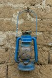 Vieille lanterne bleue rouillée de pétrole sur un mur de briques de boue photographie stock libre de droits