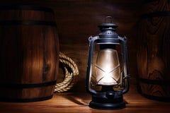 Vieille lanterne de kérosène brûlant dans un entrepôt Photographie stock libre de droits