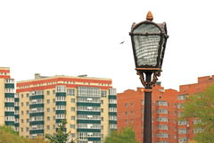 Vieille lanterne de rue de fer contre le contexte des maisons Images stock