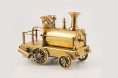 Vieille locomotive à vapeur d'or de jouet sur le fond d'isolement Photographie stock libre de droits