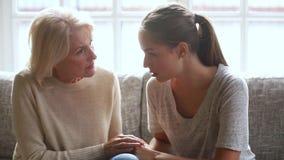 Vieille mère inquiétée écoutant la jeune fille triste partageant des problèmes clips vidéos