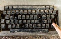 Vieille machine à écrire avec les boutons spéciaux, le mot d'AMOUR et la main de l'homme Photos stock
