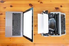 Vieille machine à écrire contre le nouvel ordinateur portable sur la table Concept de progrès de technologie photographie stock