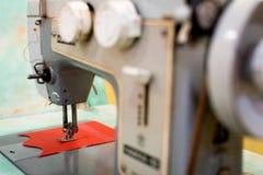 Vieille machine à coudre avec une bobine des fils cramoisis Photos stock