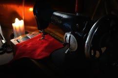 Vieille machine à coudre de volant de commande, tissu et ciseaux de mise sur pied dans t Photos libres de droits
