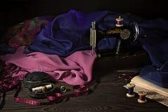 Vieille machine à coudre, tissus, ciseaux et d'autres accessoires Images stock