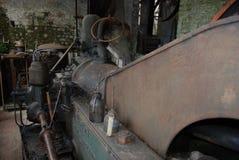 Vieille machine rouillée énorme dans le hangar avec des boîtes d'huile photographie stock