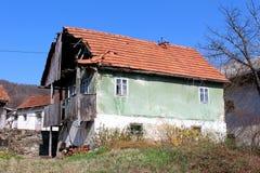 Vieille maison abandonnée de famille avec les tuiles de toit cassées et le porche en bois avant criqué démontés de la grille d'al photographie stock