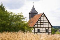Vieille maison allemande près d'un champ de blé Images stock