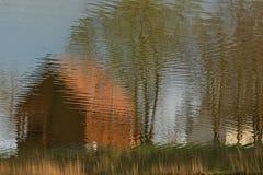 Vieille maison avec la réflexion dans l'étang Photographie stock