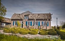 Vieille maison avec le jardin topiaire Image stock