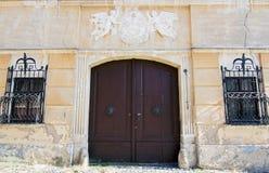 Vieille maison avec le manteau des bras au-dessus de la porte en bois Photo libre de droits