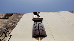 Vieille maison avec les fenêtres ouvertes avec les volets en bois contre le ciel bleu banque de vidéos
