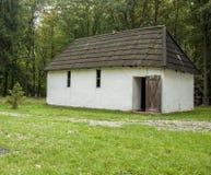 Vieille maison blanche avec un toit en bois dans la forêt Photos libres de droits