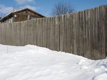 Vieille maison derrière la haute frontière de sécurité en bois en hiver Photo stock