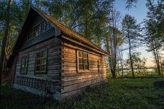 Vieille maison en bois au bord de forêt près du lac Svir au lever de soleil image libre de droits