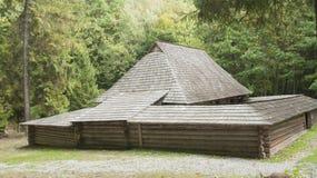 Vieille maison en bois avec le toit en bois dans la forêt, fond Photo libre de droits