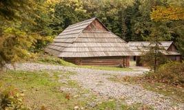 Vieille maison en bois avec le toit en bois dans la forêt, fond Photos stock
