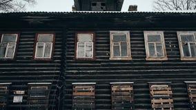 Vieille maison en bois avec les fenêtres noires Personne à l'intérieur Maison abandonnée dans le délabrement avec les fenêtres em banque de vidéos