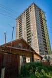 Vieille maison en bois devant un grand gratte-ciel moderne grand images libres de droits