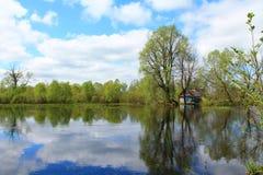 Vieille maison en bois entourée par l'eau Photographie stock