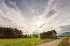 Vieille maison en bois oblique de hangar dans le pré Photographie stock