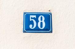 Vieille maison nombre de plaque métallique bleu d'adresse 58 cinquante-huit de vintage sur la façade de plâtre du mur extérieur a images stock