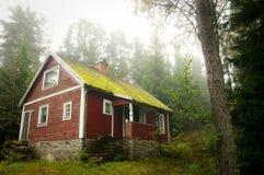 Vieille maison rouge dans la forêt. Photographie stock
